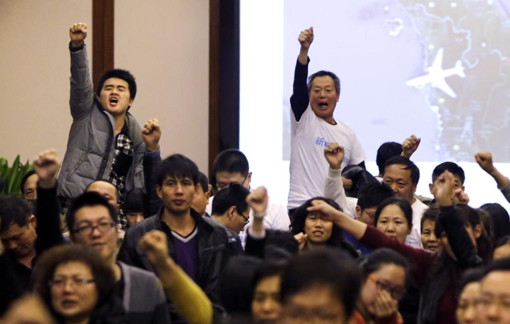 "Family members of passengers onboard Malaysia Airlines Flight MH370 raise their fists as they shout ""return our families"" to protest against the lack of new information after a routine briefing given by Malaysia's government and military representatives at Lido Hotel in Beijing March 22, 2014."