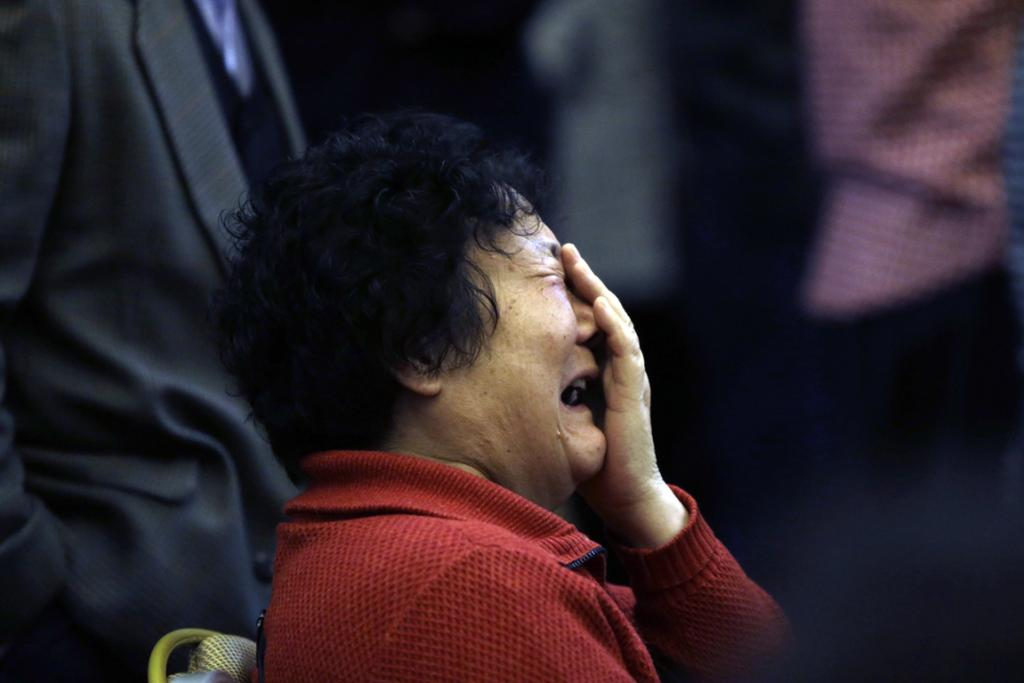 A family member of a passenger onboard Malaysia Airlines Flight MH370 covers her face as she cries after a routine briefing given by Malaysia Airlines at Lido Hotel in Beijing, March 22, 2014.