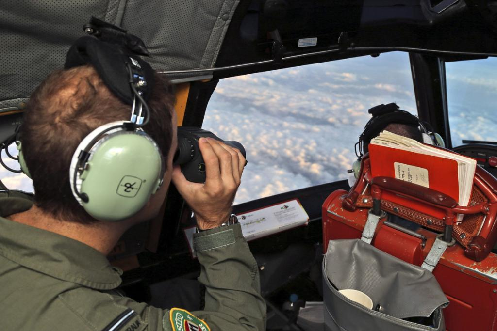 A crew member aboard a Royal Australian Air Force (RAAF) AP-3C Orion uses binoculars as it flies over the southern Indian Ocean during the search for missing Malaysian Airlines flight MH370 March 22, 2014.