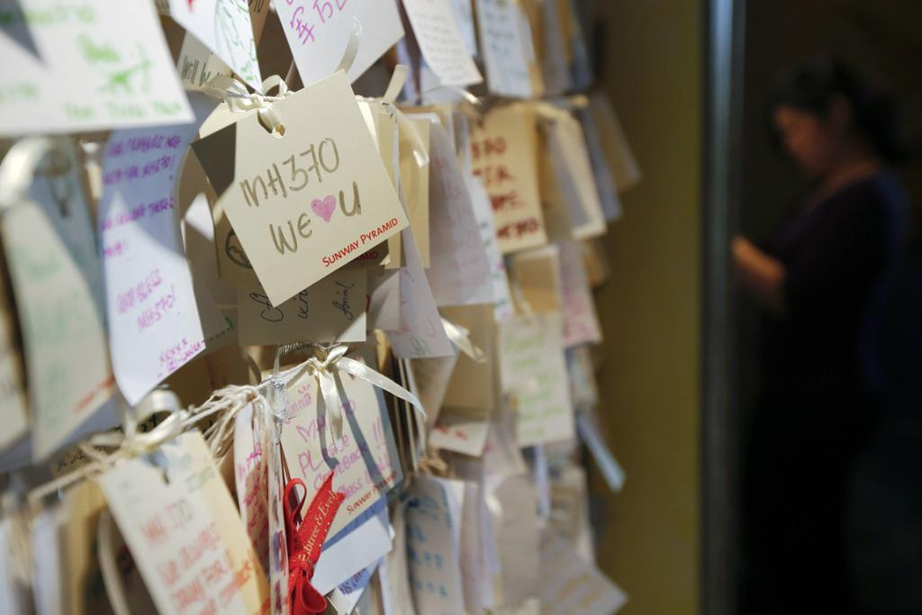 A woman writes another message of hope and support for the passengers of the missing Malaysia Airlines MH370 at a mall outside Kuala Lumpur March 22, 2014.