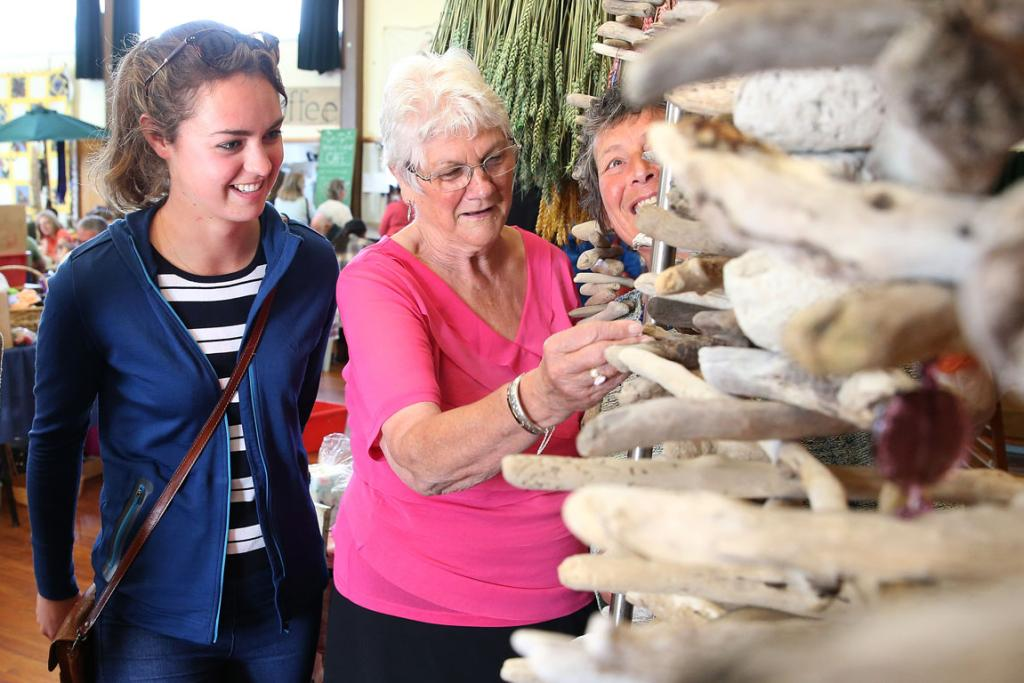 Hazel Clemens, left, of Invercargill, her grandmother Jan Clemens, of Pleasant Point, and Donnette Wohlers looking at Donnette's driftwood decoarations.