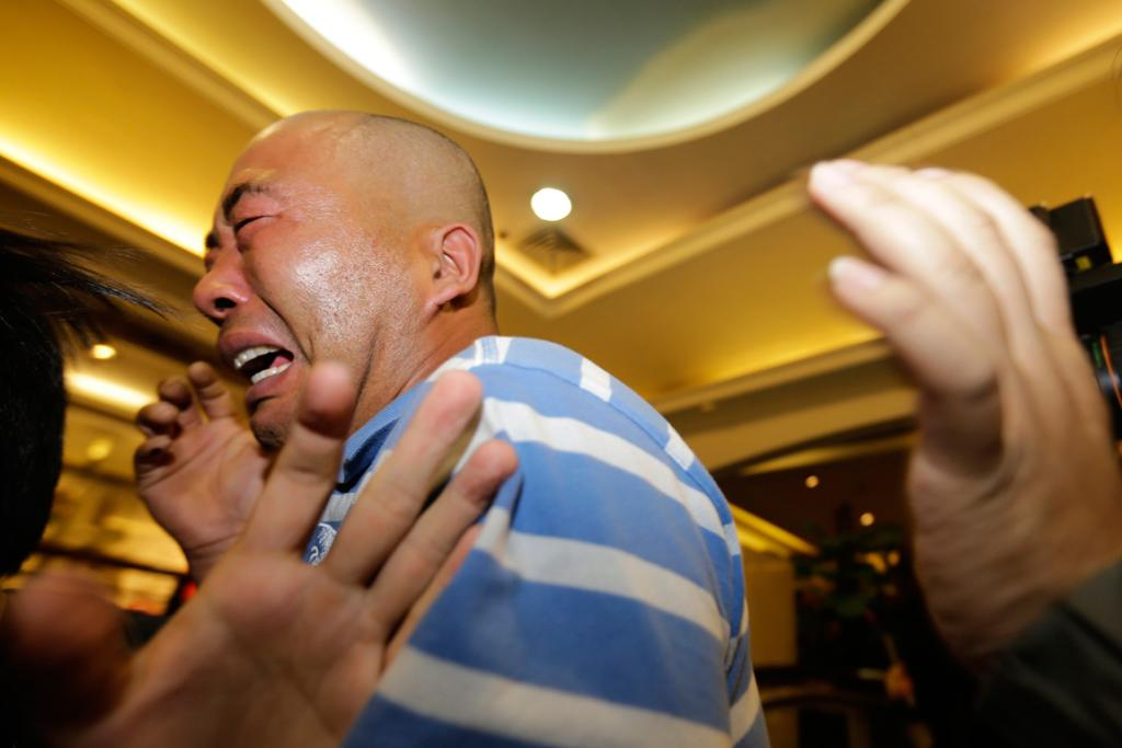 A relative of a passenger aboard Malaysia Airlines MH370 cries after watching a television broadcast of a news conference, in the Lido hotel in Beijing.