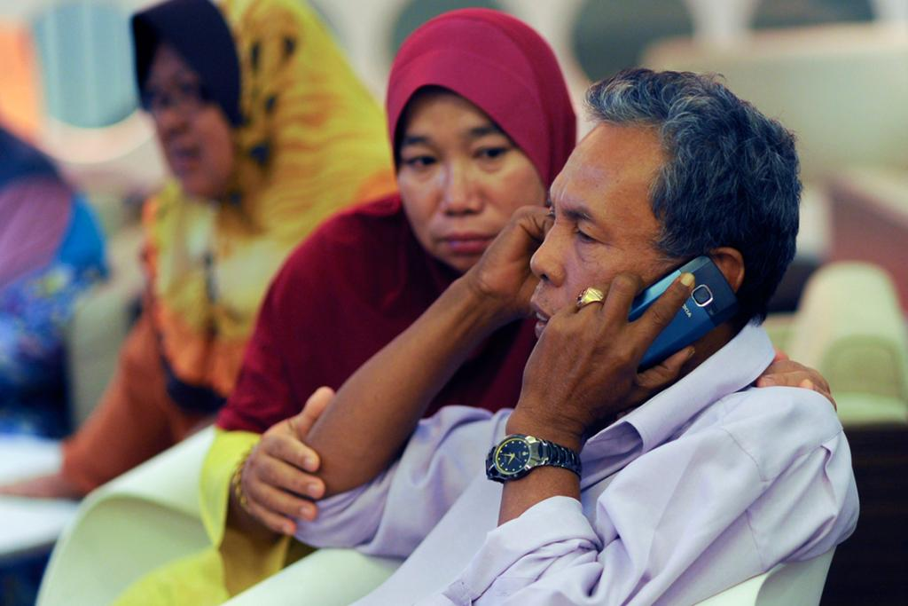 Selamat Omar (right), father of flight engineer Mohd Khairul Amri Selamat who was on board the missing Malaysia Airlines flight MH370, sits next to his wife Rosila Abu Samah as he speaks on the  phone at the hotel where he and other relatives of passengers are staying.