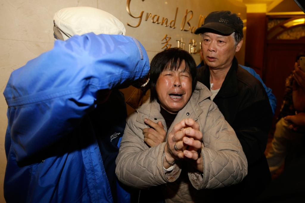 A family member of a passenger aboard Malaysia Airlines flight MH370 cries after watching a television broadcast of a news conference where Malaysia's PM announced the plane crashed in the southern Indian Ocean.