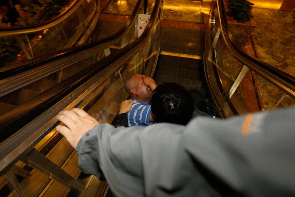 A family member of a passenger aboard Malaysia Airlines flight MH370 falls down an escalator as he cries after the news that the plane crashed in the southern Indian Ocean and there were no survivors.