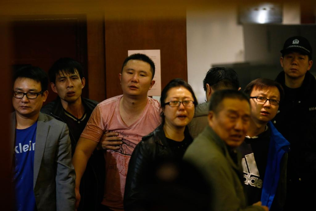 Family members of passengers aboard Malaysia Airlines MH370 look out from a room as they cry after watching a television broadcast of a news conference, in the Lido hotel in Beijing.