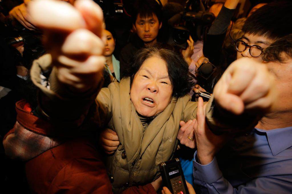 A family member of a passenger aboard Malaysia Airlines MH370 shouts at journalists after hearing the news that all hope had been lost of finding survivors of MH370.