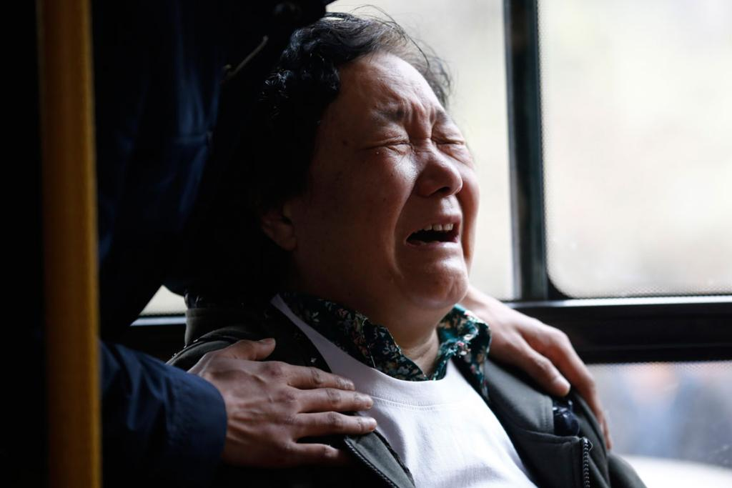 A family member of a passenger onboard Malaysia Airlines Flight MH370 cries on a bus before heading to the protest outside the Malaysian embassy, outside Lido Hotel in Beijing.