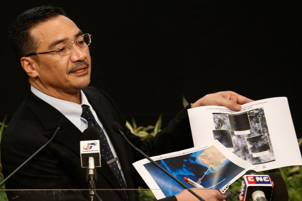 Malaysia's acting Transport Minister Hishammuddin Hussein holds satellite images as he speaks about the search for the missing Malaysia Airlines flight MH370 on March 26.