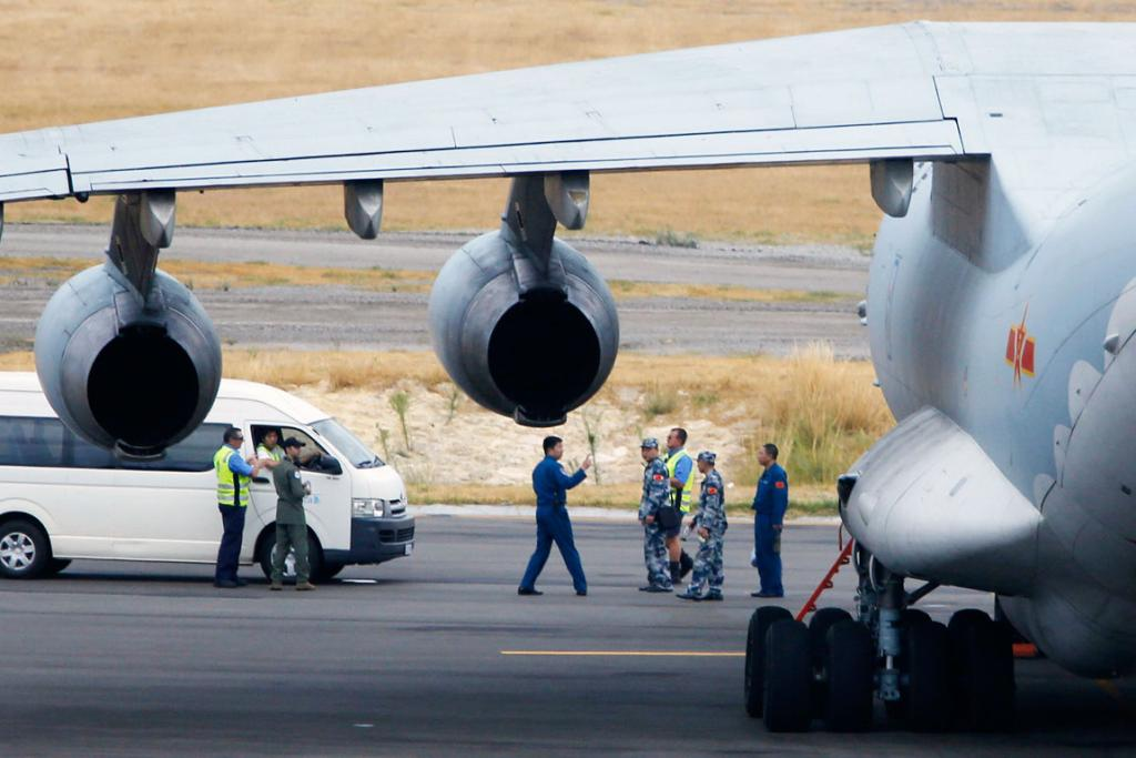 The crew of one of two Chinese Air Force Ilyushin Il-76 aircraft used in the search for Malaysia Airlines flight MH370 walk away from their plane in Perth.