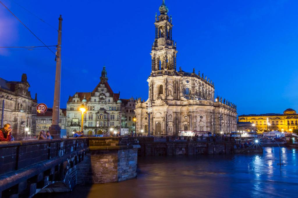 People look at the swollen Elbe rive in front of the historic skyline of the east German city of Dresden.
