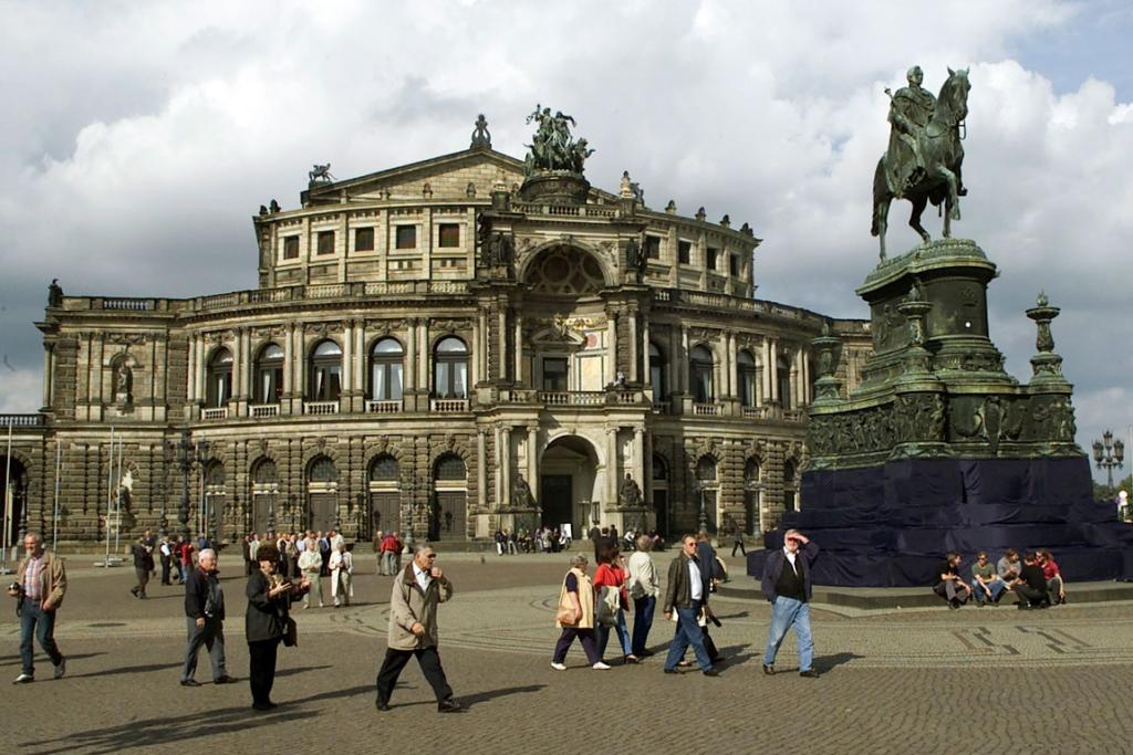 People walk past a statue of King Johann of Saxony (1801-73) in front of the Semperoper opera house.