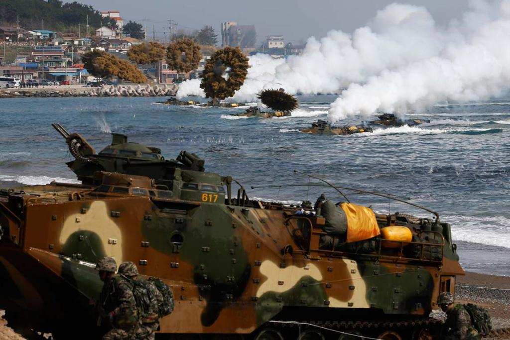 Amphibious assault vehicles of the South Korean Marine Corps throw smoke bombs as they move to land on shore during a US-South Korea joint landing operation drill in Pohang March 31, 2014.