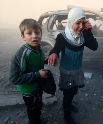 TERROR: A girl cries near a damaged car at a site hit by what activists said were barrel bombs dropped by government forces in Aleppo's Dahret Awwad neighbourhood in January 2014.