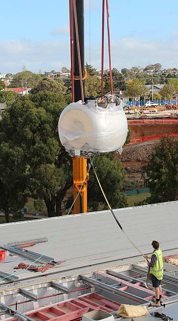 SHE'S HEAVY: The 5.5-tonne MRI magnet is craned into North Shore Hospital through the roof.