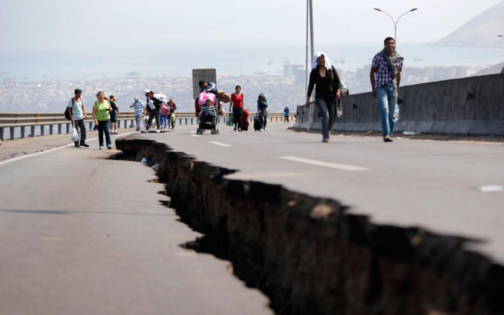 People walk next to a crack along a damaged road leading to Alto Hospicio commune, after a series of aftershocks, in the northern port of Iquique April 3, 2014.