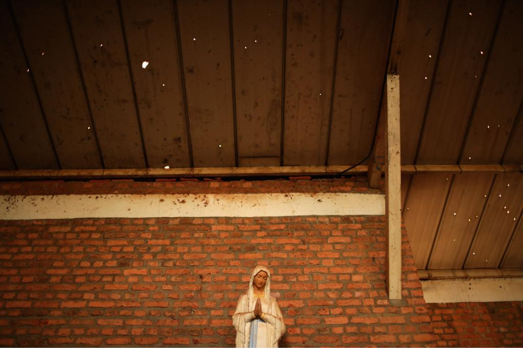 Bullet holes pock the roof above the head of a statue of the Virgin Mary inside the Nyamata Catholic Church genocide memorial, where 5000 were killed.