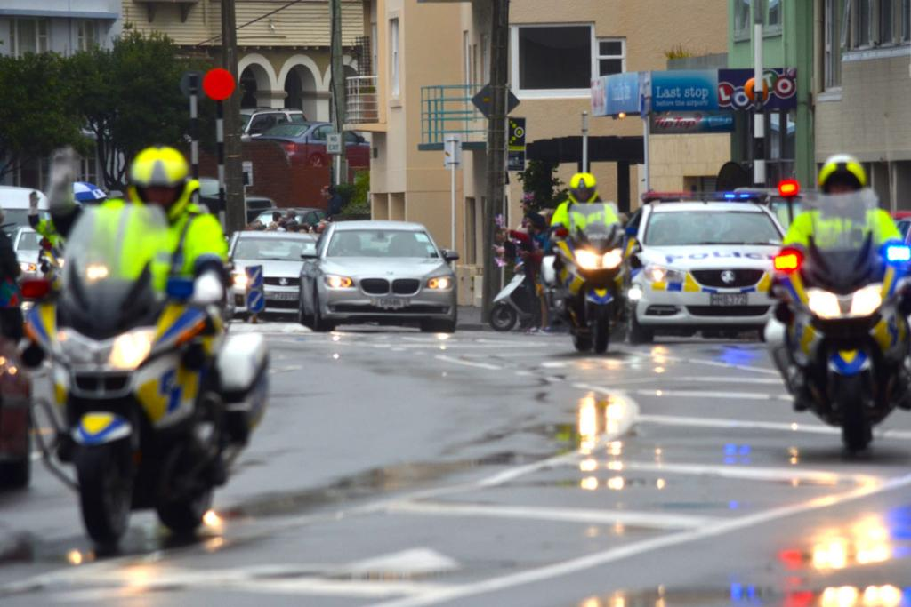 Riders in the storm. Police guide the royal entourage around Oriental Parade to Government House.