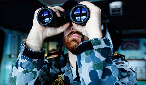 HUNT CONTINUES: Maritime Warfare Officer, Sub Lieutenant Officer Samuel Archibald, looks through binoculars on the bridge of the Australian Navy ship HMAS Perth in the southern Indian Ocean, during the search for the missing Malaysian Airlines flight MH370.