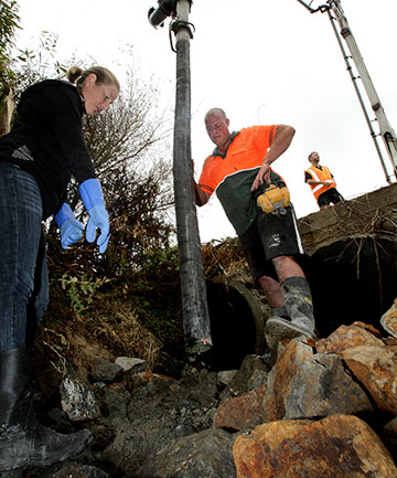CLEAN UP: Fish passes are installed in a stream by a culvert in Kingston Road near Shannon. Lucy Ferguson, Freshwater Coordinator, Horizons Regional Council, supervises the placement of concrete, amongst the rocks, being pumped from the truck by Dave Teal of Manawatu Concrete Pumping.