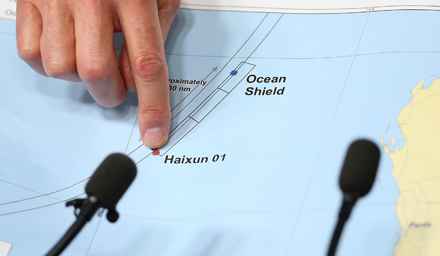 Australian Air Chief Marshal Angus Houston (ret'd) on Monday holds a map outlining the current search areas of naval ships Ocean Shield and Haixun 01.