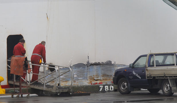FERRY TROUBLES: A gash of about five metres can be seen along the port side of the Stena Alegra, above the water line. Workers can be seen using a gas torch to repair the gash.