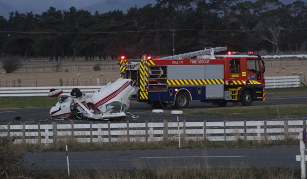 CRASH SITE: Two people were in the plane when it hit a digger and crashed near the airfield.