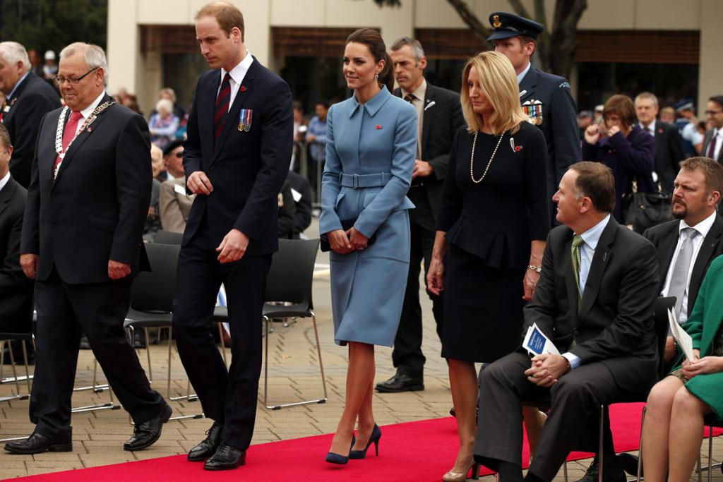 Prime Minister John Key, seated, looks on as William and Kate walk past.