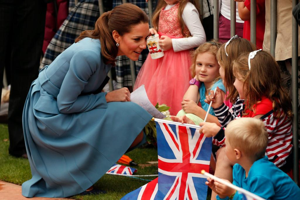 Catherine, Duchess of Cambridge, talks with some children after laying a wreath with her husband, Britain's Prince William.