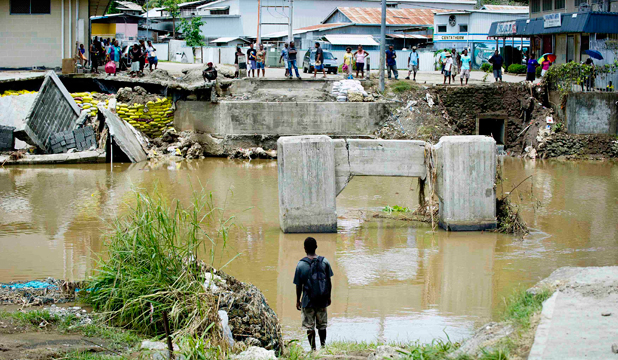 DEVASTATED: Locals look at a bridge that was destroyed as a result of severe flooding near the capital of Honiara in the Solomon Islands.
