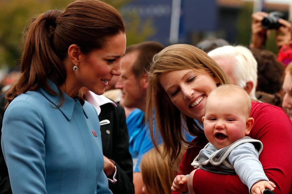 Catherine reacts as she meets a baby in the crowd after laying a wreath with her husband.