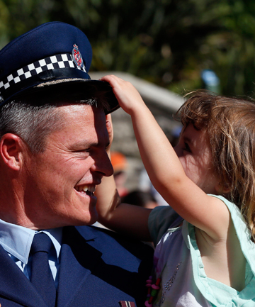 IF THE CAP FITS: Tasman police district commander Superintendent Richard Chambers is about to lose his hat to his daughter Macy Chambers, 3, at the First Responders parade at the top of Trafalgar St.