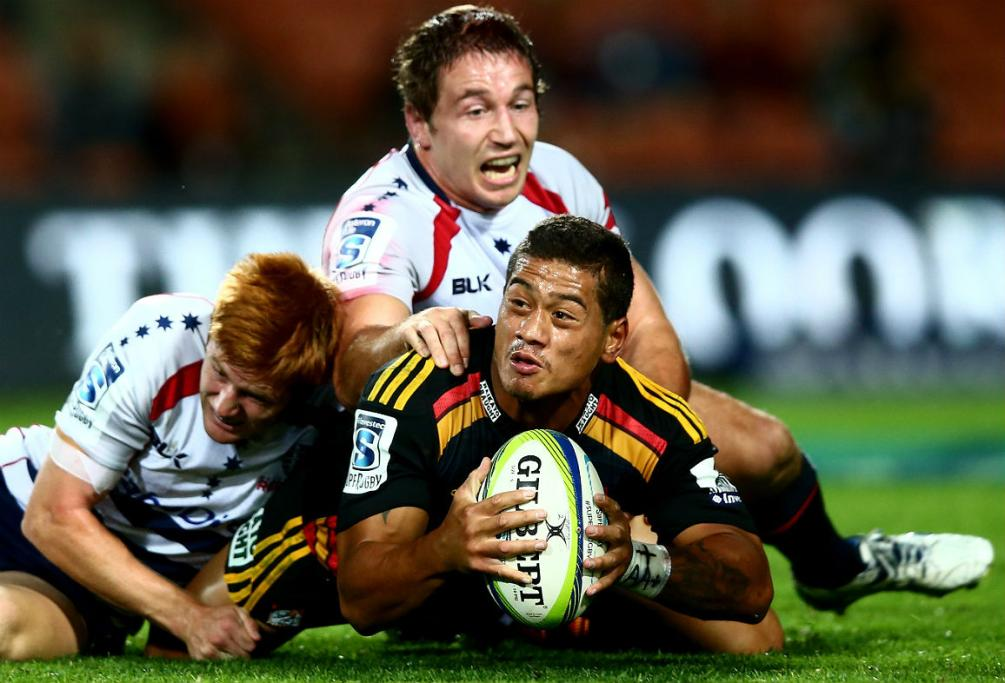 Chiefs halfback Augustine Pulu looks to offload after being grounded by the Melbourne Rebels' defence.