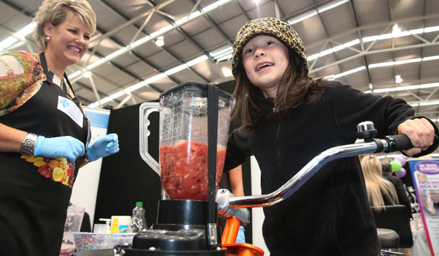 Pedalling her way to fitness by making a smoothy attached to the bike is Samantha Cooper, 8, of Invercargill, with Alison Young, left, at the Southern Cross stall at the Woman's Lifestyle Expo.