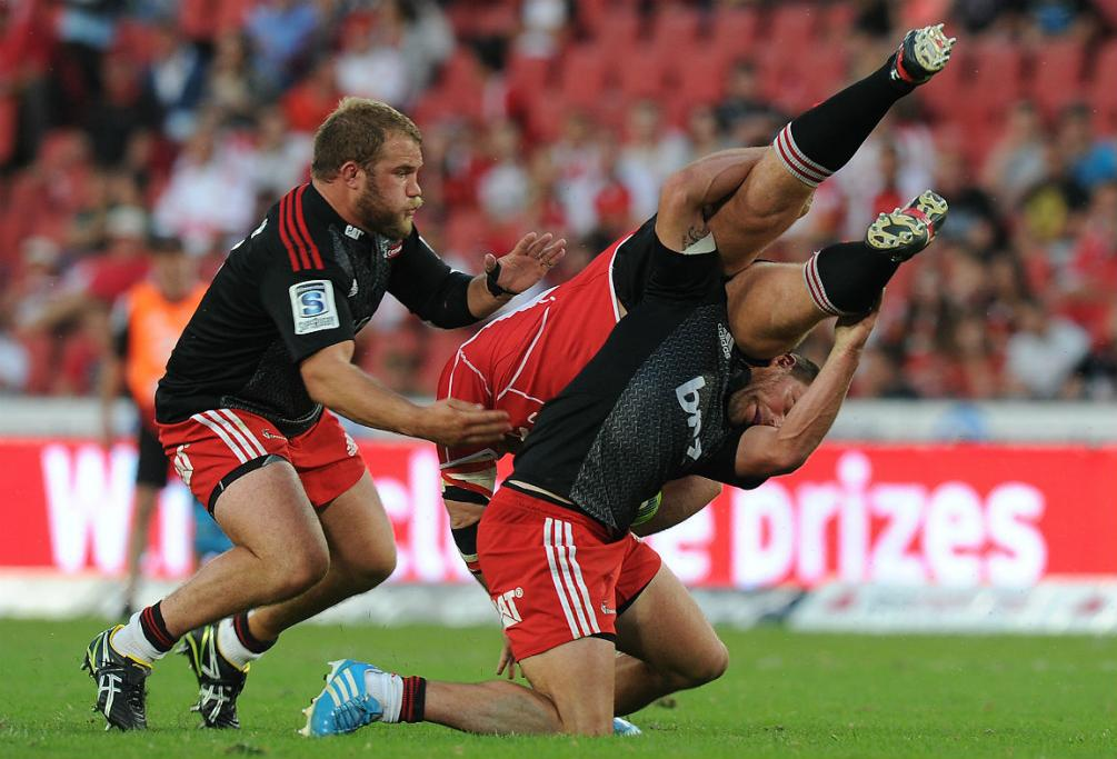 The Crusaders' Kieron Fonotia and Owen Franks get to grips with Schalk van der Merwe of the Lions.