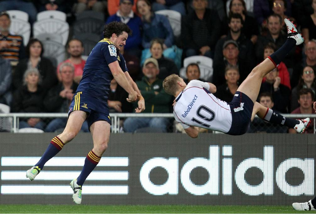 Richard Buckman of the Highlanders and Bryce Hegarty of the Melbourne Rebels dance in mid air for possession of the ball.