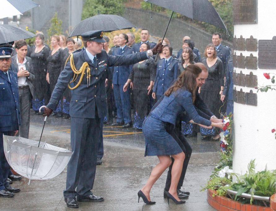 Formal duties can't wait for sunshine, with a serviceman doing his best to keep Wills and Kate dry as they lay a wreath at the police college's remembrance wall.