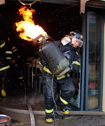 FLAMING MAD: Firefighter Huangpu Jiangwu hugs a burning gas cylinder as he removes it from the site of a fire incident in Wuhan, Hubei province.