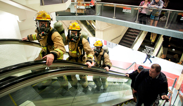 HARD TASK: Feilding firefighters, from left, Caleb Gardner, Jonathon Bunn and Daniel Pinfold, walk the wrong way up an escalator in Downtown on Broadway Ave, Palmerston North, as a fundraiser for the Leukaemia and Blood Foundation.