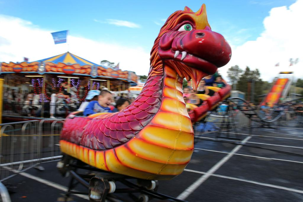 A dragon takes children for a spin at the Royal Easter Show in Auckland.