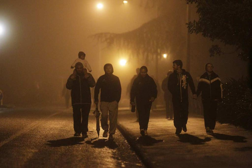Members of the public walk through the fog in Hamilton to head to the dawn service.