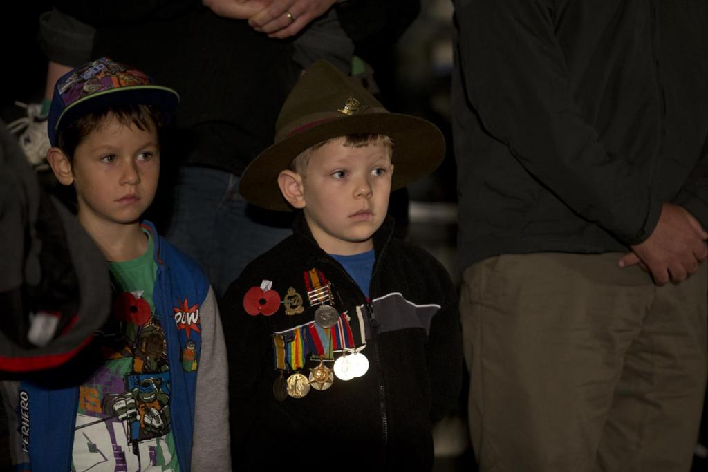 6 year old Josh Sheppard wears his great grand fathers WWI medals at the Anzac Dawn Service at the Domain
