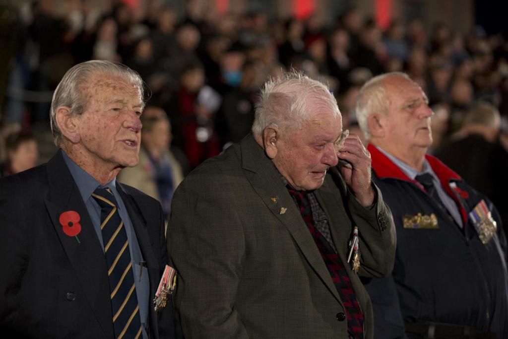 WWII veterans stand to attention during the singing of the New Zealand National Anthem during the Anzac dawn service at the Domain