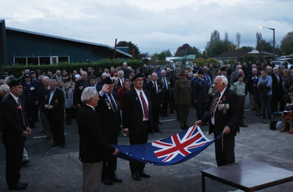 Dawn parade at Motueka cenotaph. Members of the RSA pay their respects as they lay a poppies in the flag.