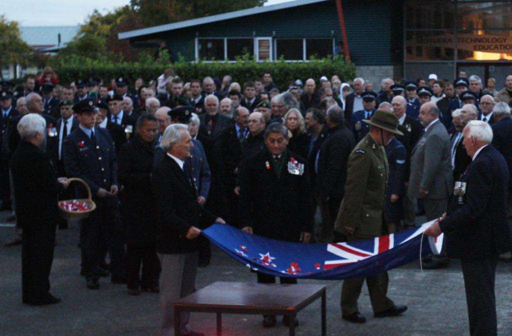 Dawn parade at Motueka cenotaph. Moeke Paaka pays his respects as he lays a poppy in the flag.