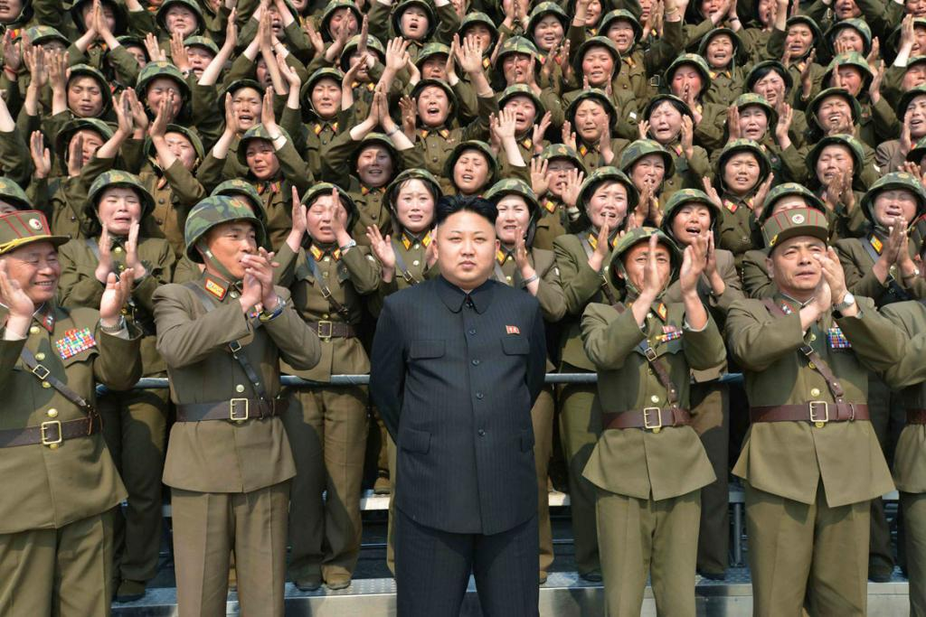 """""""Being a dictator is so hard, but boy can I pull off the steely-eyed pose. The camera loves me. You guys in the back, raise the roof!"""""""