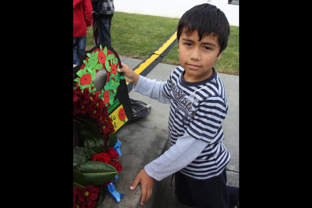 Waiuku Primary School pupil Ben Cutler, 6, places a wreath created by his fellow students at the Waiuku cenotaph.