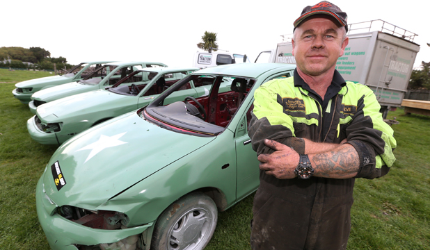 THE FLEET: Defending champion Steve Clements with the four cars he has entered for the demolition derby at Riverside Speedway, near Invercargill, today.