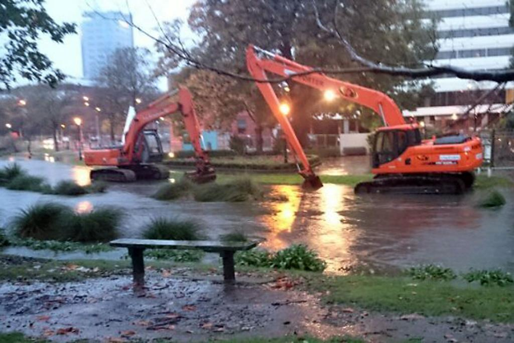 SINKING: Diggers under water as the Avon River spills over.