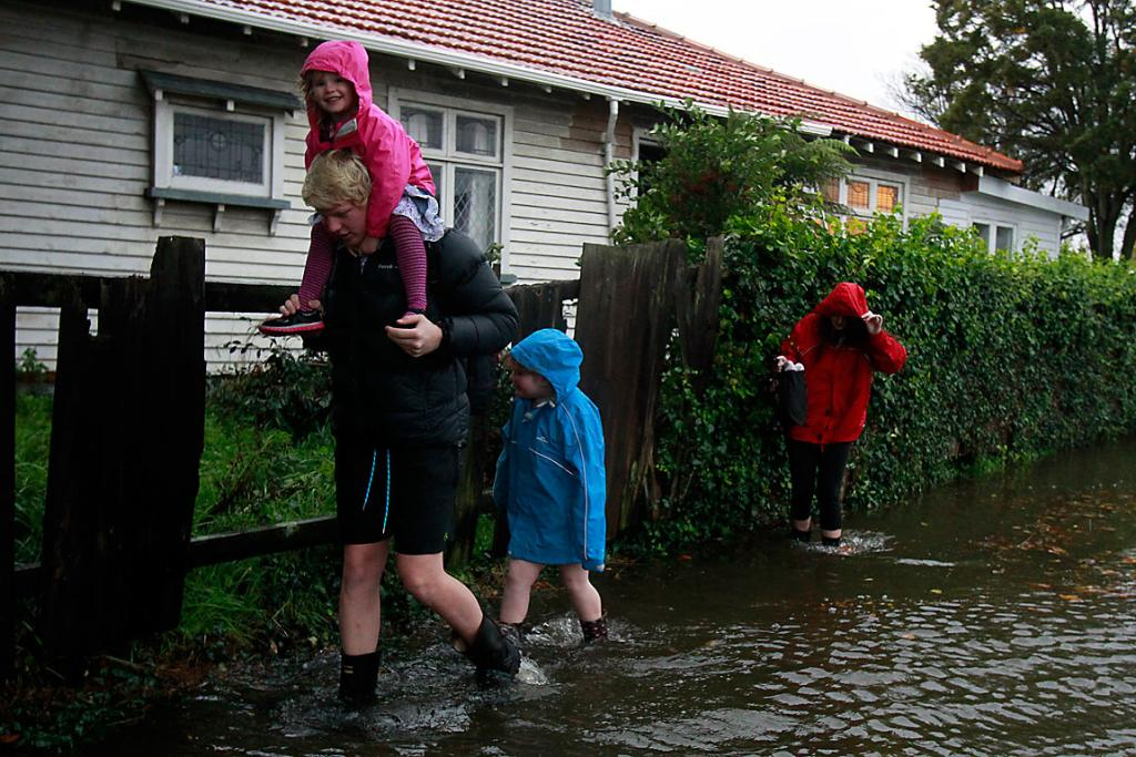 WET WALK: Zach Williams carries Jessica Curtis on his shoulders followed by Emma Curtis and Becky Douglas as they walk down Archers Street.
